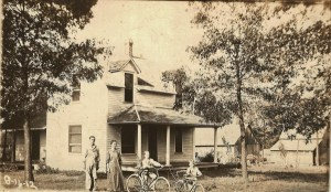 dated on front 8-16-1912, house with man, woman, 2 boys with bicycles